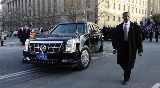U.S. Secret Service officers escort the presidential limousine down Pennsylvania Avenue enroute to the White House