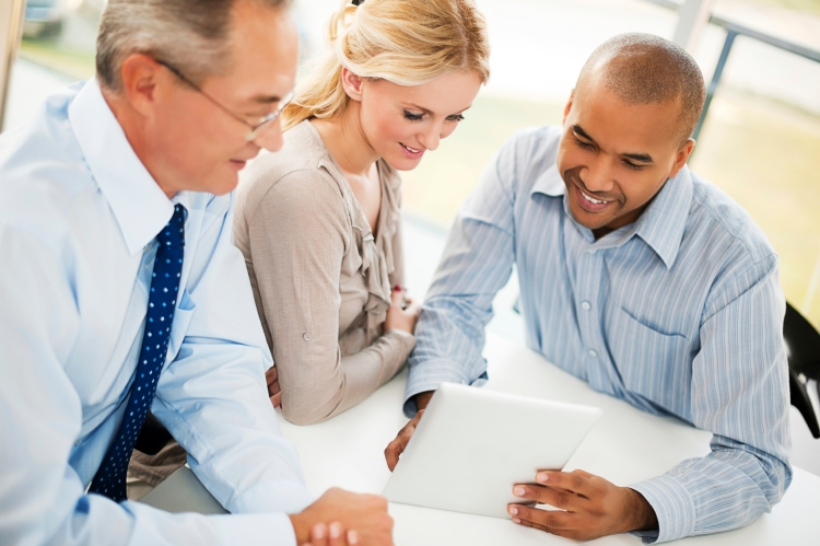 Three businesspeople looking on a touchpad.